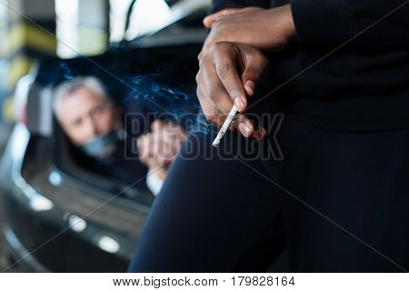 Tobacco product. Selective focus of a half smoked cigarette being in hands of a smart dangerous criminal
