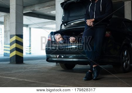 Nothing to worry about. Calm relaxed adult man leaning on the car boot and enjoying his cigarette while waiting looking at his hostage