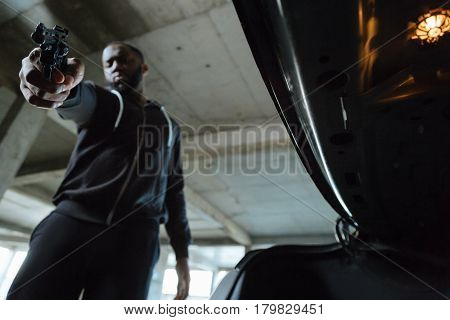 Life in danger. Serious bearded ruthless man standing in front of the car boor and intending to kill you while holding you at gunpoint
