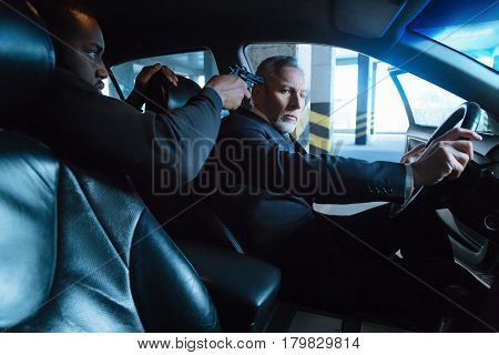 Drive the car. Handsome shocked senior businessman being threatened and being ordered to drive the car while becoming a victim of kidnapping