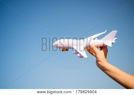 White Toy Plane In Female Hand On Sunny Blue Sky
