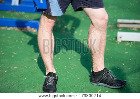 Man Muscular Legs In Black Sport Fashion Shoes At Stadium