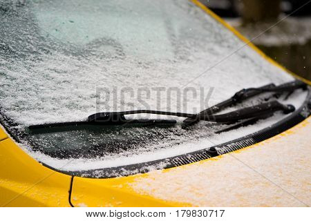 Wiper and windscreen of the parked car covered with snow. Close up.