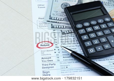Tax form, calculator and dollars on table