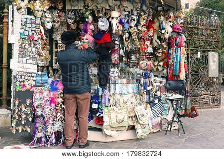 VENICE ITALY - JANUARY 09; Man standing in front of large street kiosk with souvenirs tourists are buying when they come to Venice Italy - January 09 2017: Venice is one of the most visited tourist destinations around the world.