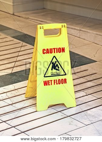 Plastic wet floor sign on marble surface