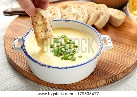 Female hand dipping slice of bread in saucepan with beer cheese dip