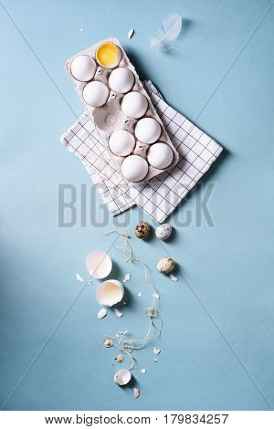 Egg white eggs or chicken eggs in a pack for eggs, quail eggs, food background. Cracked egg with white and yolk over blue. Spring easter theme.