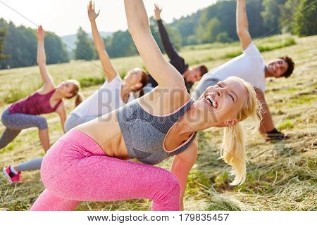 Woman having fun in aerobics class with friends in summer