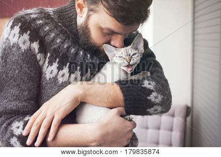 Happy young man is standing on a balcony with his cat. Home pets. Beautiful man is holding and hugging his cute curious devon rex cat with blue eyes