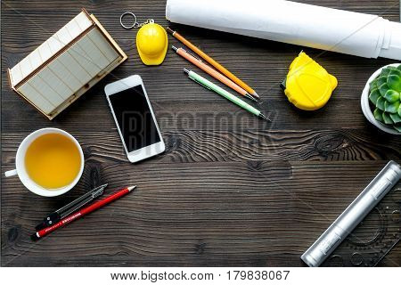 architect working desk with mobile, cup of tea, project and pens on wooden background top view mock up