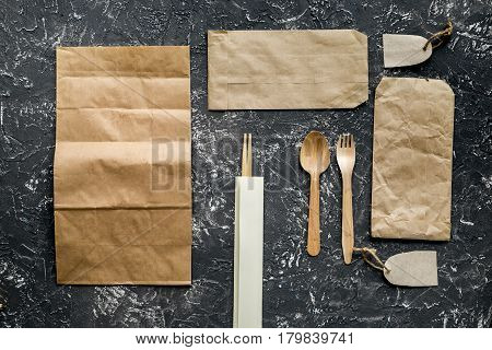 food delivery service workdesk with paper bags and flatware on gray background top view