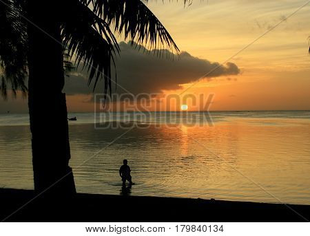 Wading out at sunset A boy wades into the golden waters reflected by the setting sun in Saipan, Northern Mariana Islands.