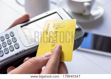 Payment in cafe for business lunch concept with credit card and terminal on white desk background