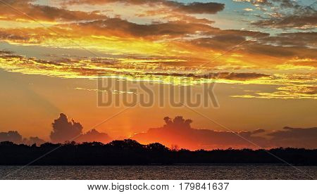 Colorful Sunset in vicinity or Frazer Island with both Cumulus and Stratocumulus clouds highlighted. This photograph was taken over tropical water Queensland, Australia. sunset sun dusk gold crimson seascape waterscape saltwater reflections silhouettes cl