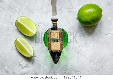 green absinthe in glass with fresh lime slices on stone table background top view