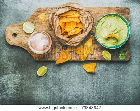Fresh guacamole sauce in blue ceramic bowl, mexican corn chips, glass of wheat beer on rustic wooden serving board over grey concrete table background, top view, copy space, horizontal composition