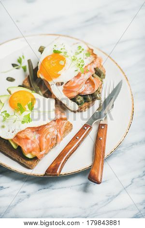 Healthy breakfast sandwiches. Salmon, avocado, fried egg, sauted green beans and fresh sprouts sandwiches in white plate over marble background, selective focus. Clean eating, weight loss food concept