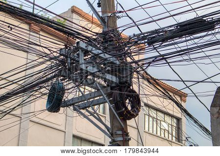 Many electrical wires on pillar. Asian urban electric supply. Industrial electrification pole with wire mess. Internet connection infrastructure. Electric pillar closeup photo. High voltage concept