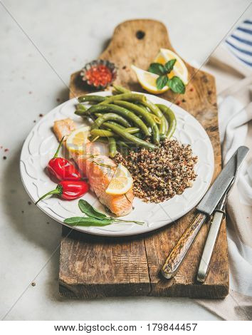 Healthy protein rich dinner plate. Oven roasted salmon fillet with multicolored quinoa, chilli pepper and poached green beans on rustic wooden board over grey marble background. Clean eating food