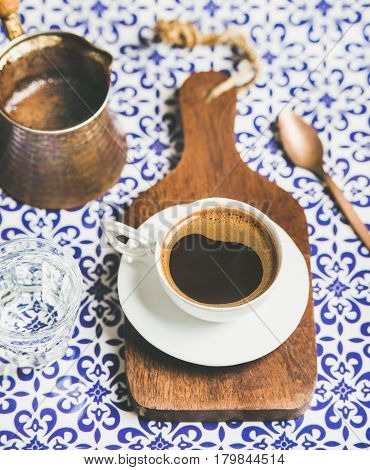 Cup of black Turkish or Eastern style coffee on wooden serving board over oriental bright motley Moroccan patterned background, selective focus
