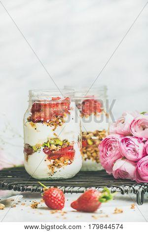 Healthy spring breakfast. Greek yogurt, granola, fresh strawberry breakfast in jars, pink raninkulus flowers, marble background, selective focus, copy space. Clean eating, detox food concept