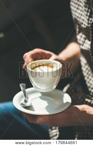 Cup of coffee cappuccino in man's hands in street cafe under sunlight, copy space