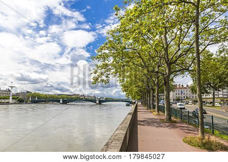 Enbankment of the Rhone river in center of Lyon city Auvergne-Rhone-Alpes region France. University Bridge (Pont de l'Universite) on the background