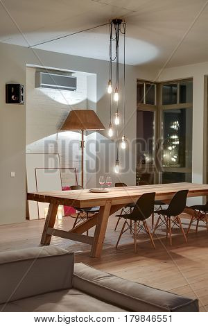Luminous room in a modern style with light walls and a parquet on the floor. There is a large wooden table with black chairs, sofa, stylish lamp with a lampshade, hanging lamps, speaker, conditioner.
