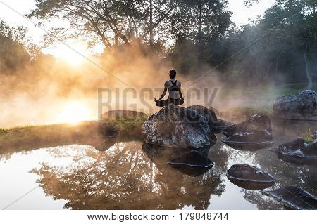 Young woman in silhouette practice yoga in a hot spring