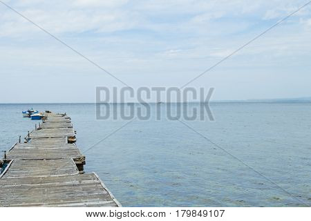 Still sea with boat and wooden pier landscape. Romantic seaside view toned photo. Rustic timber pierce in still sea. Summer holiday seascape trendy banner template with text place. Seashore background