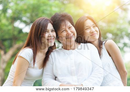 Portrait of happy Asian elderly mother and her daughters, senior adult woman and grown child. Outdoors family at nature park with beautiful sun flare.
