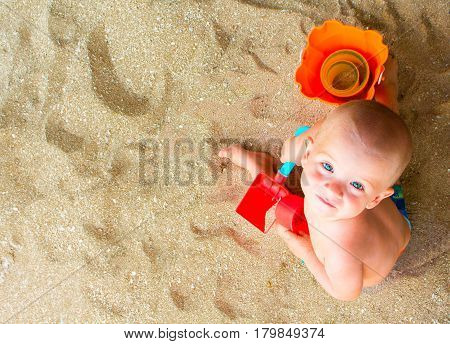 Child plays with sand on beach. Cute baby boy on white beach. Tropical seaside vacation with baby. Blue eyes boy on summer holiday. Child with red scoop and bucket photo. Childhood on seaside banner