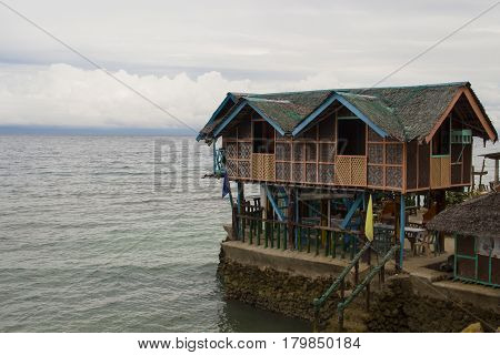 Wooden house on piles in shallow sea water. Traditional house in Philippines. Seaside scene with eco lodge in sea. Minimalist resort banner template with text place. Philippines island hopping travel