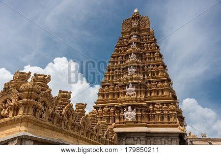Nanjangud India - October 26 2013: The main Gopuram of Sri Srikanteshware temple in Ganjangud Karnataka State. Part of the decorate Mandapam roof in front. Golden decoration white statues. Cloudscape.