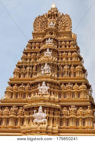 Nanjangud India - October 26 2013: Top six levels of main Gopuram of Sri Srikanteshware temple in Ganjangud Karnataka State. North side. Golden decoration white statues.