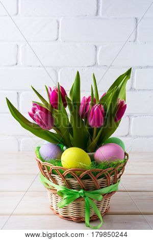 Easter table centerpiece with pastel color hand painted eggs in basket. Happy Easter greeting card. Copy space.