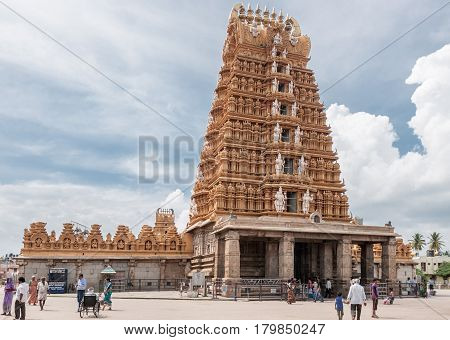 Nanjangud India - October 26 2013: The tall beige Gopuram with temple walls and small mandapam in front of the Sri Srikanteshwara Temple in Ganjangud Karnataka State. A few people on the square in front.