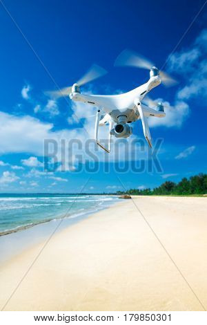 drone flying over sea. white drone hovering in a bright blue sky. New technology in the aero photo shooting.