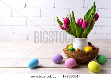 Easter table centerpiece with decorated eggs in nest. Happy Easter greeting card.Copy space.