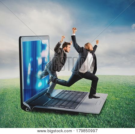 Businessmen leaves the screen of a computer to a lawn. Technology addiction concept