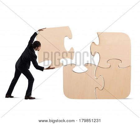 Businessman complete a big puzzle inserting a missing piece
