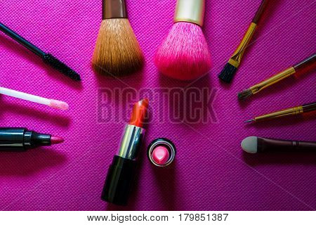 set of cosmetics on a pink background