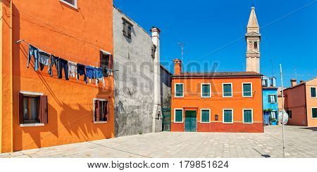 Panoramic view of small courtyard and colorful houses under blue sky of Burano, Italy.