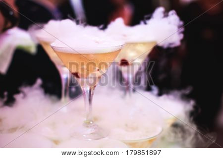 Beautiful row line of different colored alcohol cocktails on a party, martini, vodka, and others on decorated catering bouquet table on open air event, picture with beautiful bokeh