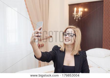 Businesswoman taking self portrait in hotel room