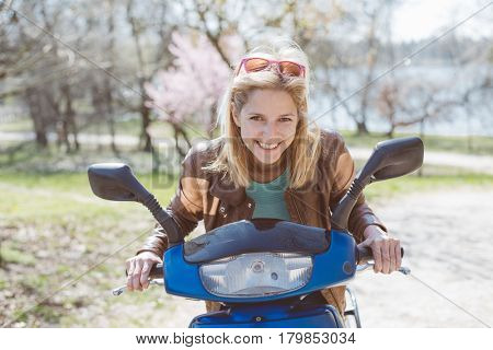Happy young woman riding on scooter