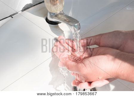 Woman washing hand with light of sun form park health care concept