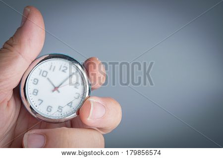 Male hand holding clock. Time management concept. Time control planning.