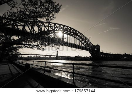 The Hell Gate Bridge and Triborough bridge over the river with walkway at Astoria park in black and white style, New York